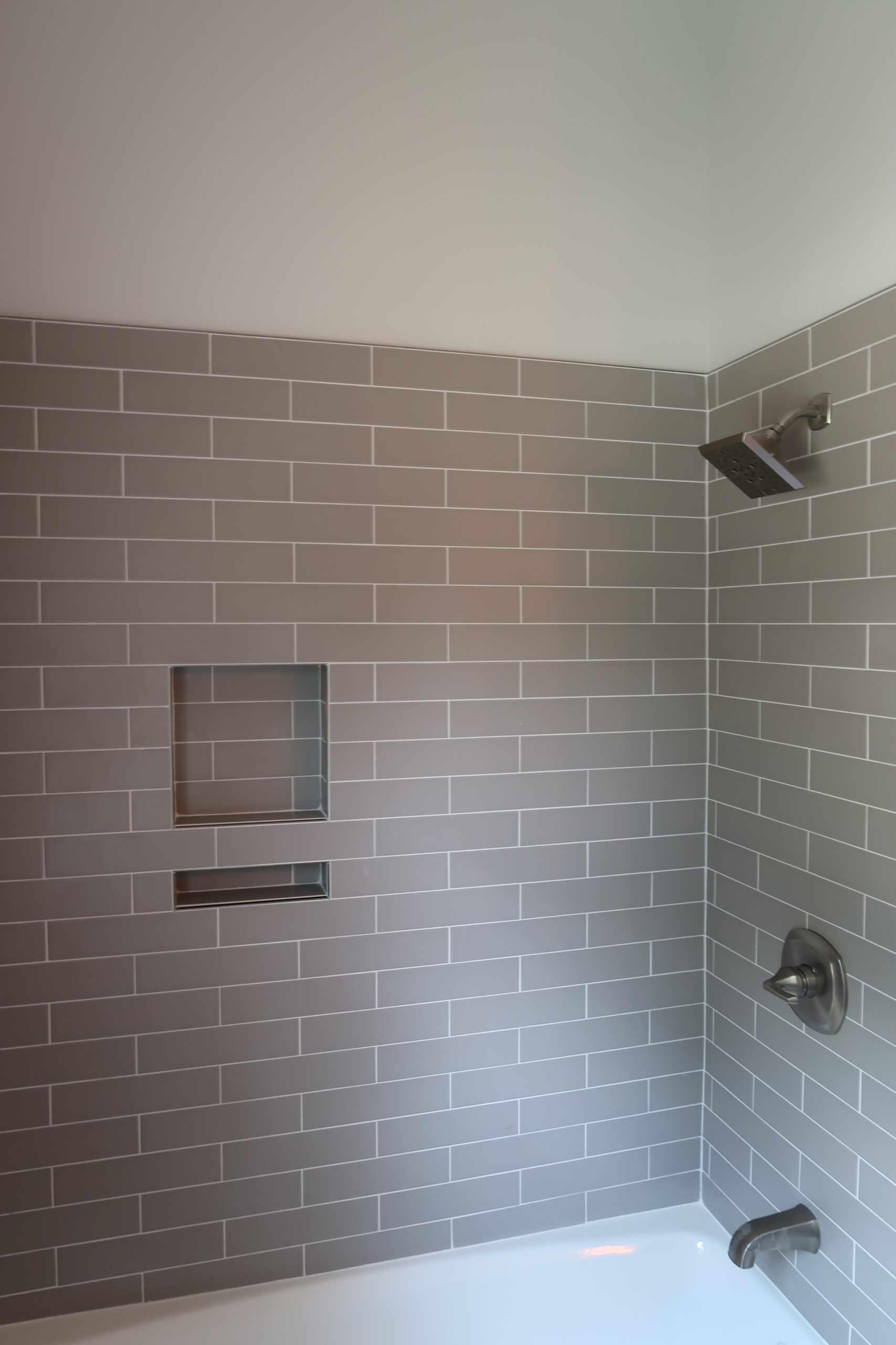 Large Grey Subway Tile and Stainless Fixtures